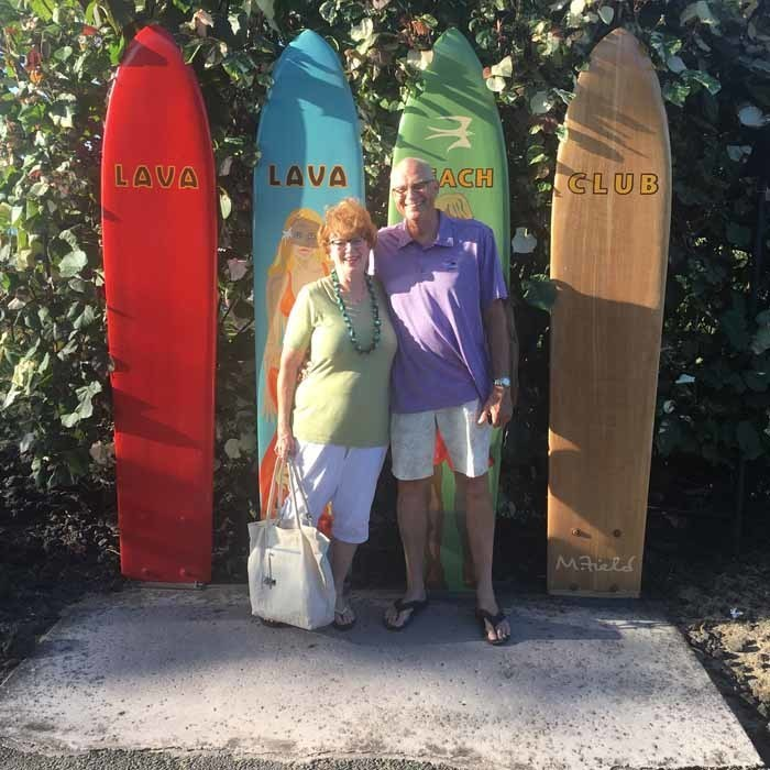 Bobby with Wife in front of Surfboards